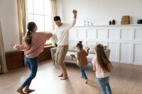 Young family dancing around the living room